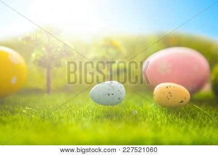 Decorated Easter Eggs In Green Grass On A Sunset Sky Background.