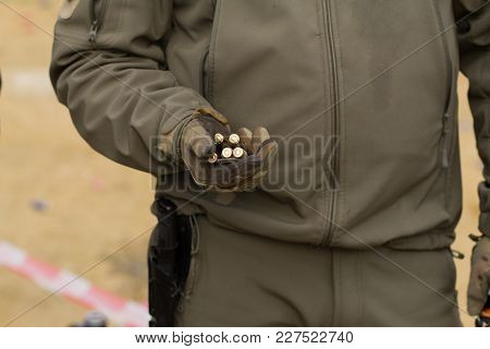 Soldier Or Hunter In Green Uniform With Ammo In Hand