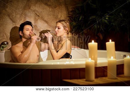 Couple Resting In Bath Tub With Candles In Spa Center. Romantic Evening Of A Couple In Love.
