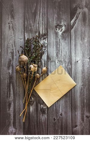 A Bouquet Of Dry Poppy Head Of Dried Mint Lies On A Black Wooden Background And An Envelope And Ther