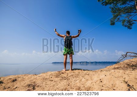 Male Traveler With Their Hands Up On Top With A Backpack And A Camera Over The Water