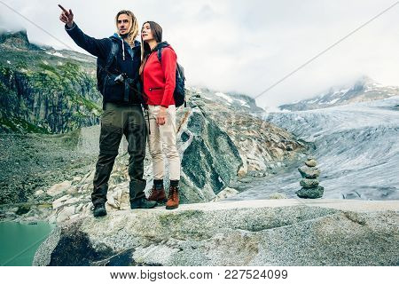 Young Couple Hiking In The Swiss Alps. Shot Taken In Swiss Alps, Near Rhone Glacier And Furka Pass.