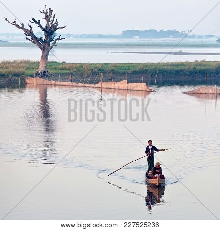 Amarapura, Myanmar - January 13, 2011: Fishermen On Wooden Boat Catching Fish For Food On Thaungtham