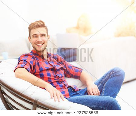 happy young man sitting in a big chair on blurred background