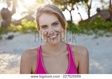 Outoor Shot Of Beautiful Sporty Female With Warm Pleasant Smile, Dressed In Top, Sunbathes On Sandy