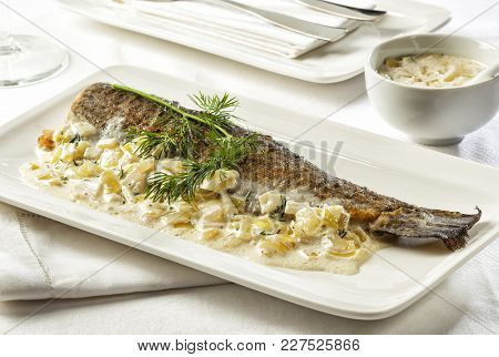 Fried Trout With Sauce Garnished With Dill.