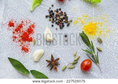 Pinches Of Dry Spices, Cherry Tomatoe, Garlic Cloves And Fresh Herbs On A Light Stone Background Wit