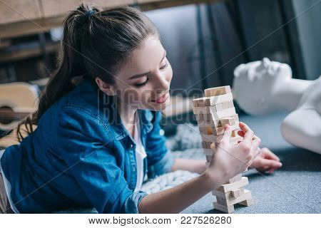 Selective Focus Of Woman Playing Blocks Wood Game With Layman Doll Near By At Home, Perfect Relation