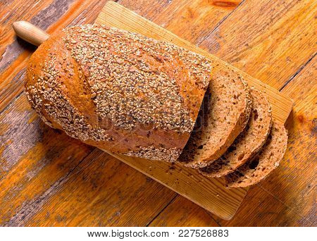 Whole Wheat Bread With Sesame And Poppy Seeds On A Cutting Board. Top View.