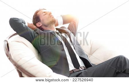 young businessman meditating in big comfortable armchair