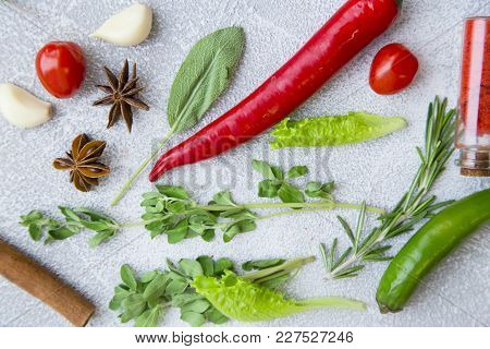 Fresh Herbs, Cherry Tomatoes, Chilli Peppers And Cinnamon Stick On A Light Stone Background With Cop