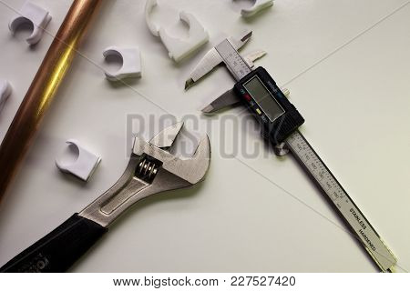 Plumber Assembles Copper Pipes, Cutter And Plastic Fixings On Work Bench