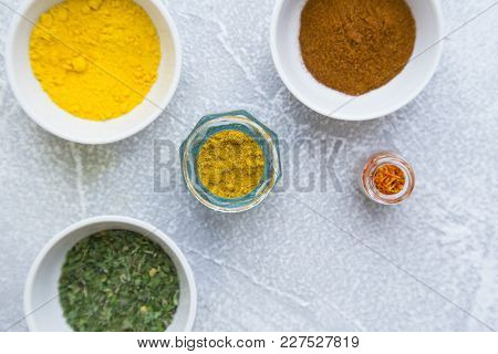 Dry Spices And Herbs In Glass Jars With And Ceramic Bowls On A Light Stone Background With Copy Spac
