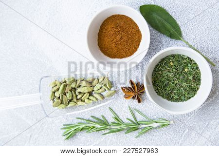 Dry Spices, Beans And Herbs In Ceramic Bowls And Glass Spoon, Fresh Herbs On A Light Stone Backgroun