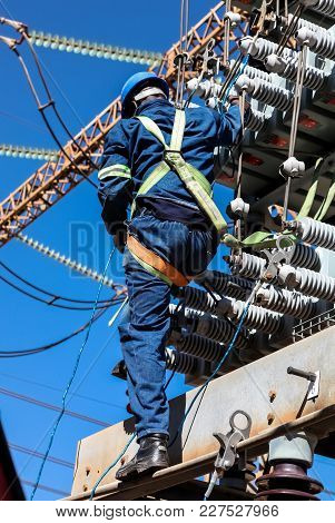 Skilled Electrician Working On High Voltage Electrical Lines At An Electricity Transmission Facility
