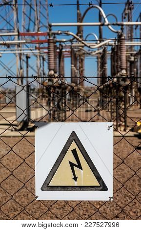 Danger Warning Sign On A Fence Outside An Electricity Transmission Facility