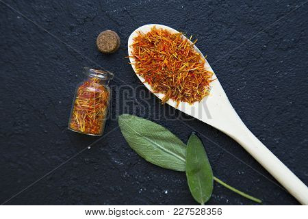 Dry Spices In A Wooden Spoon And Glass Jar , Fresh Herbs On A Black Stone Background With Copy Space