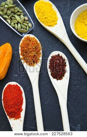 Dry Spices And Beans In Wooden And Glass Spoons, Black Stone Background With Copy Space, Top View