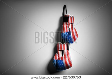Boxing gloves colored in USA flag hanging on grey wall. Concept of national power and strength