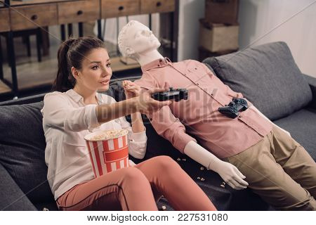 Young Woman Eating Popcorn While Playing Video Game With Manikin Near By At Home, Loneliness Concept