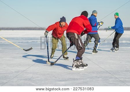 Dnepr, Ukraine - January 22, 2017: Group Of Ordinary People Playing Hockey On A Frozen River Dnepr I