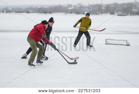 Dnipro, Ukraine - January 28, 2018: Young Man Fight With Mature Man For The Puck While Playing Hokey