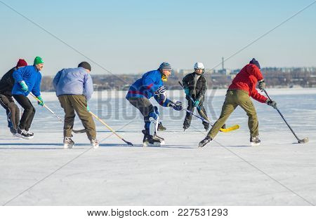 Dnepr, Ukraine - January 22, 2017: Group Of Different Ages People Playing Hockey On A Frozen River D