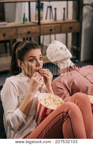 Scared Woman Eating Popcorn While Watching Film Together With Manikin At Home, Perfect Relationship