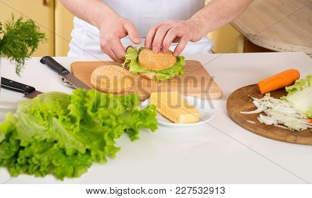 Close-up Of Male Hands Preparing Food. A Man Is Preparing A Sandwich With Cheese And Green Lettuce L