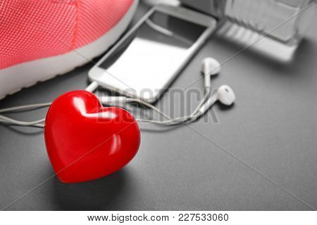 Gym stuff, phone and red heart on grey background. Cardio training concept