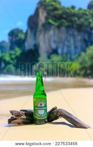 Krabi, Thailand - July 28 2017 Green Bottle Of Heineken Lager Beer With Paradise Beach Ocean Island
