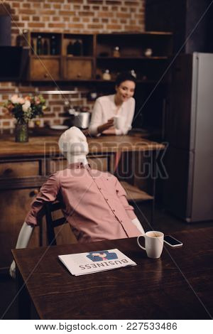 selective focus of young woman with cup of coffee and manikin at table in kitchen, perfect relationship dream concept poster