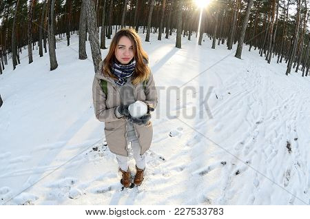 A Young And Joyful Caucasian Girl In A Brown Coat Holds A Snowball In A Snow-covered Forest In Winte