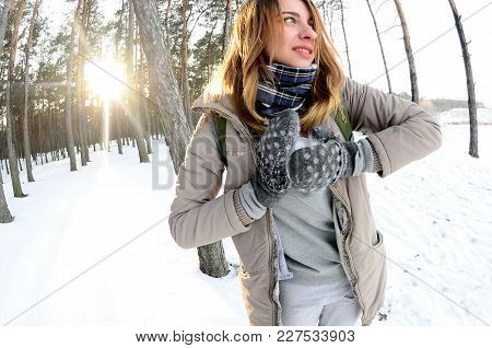 A Young And Joyful Caucasian Girl In A Brown Coat Sculpts A Snowball In A Snow-covered Forest In Win