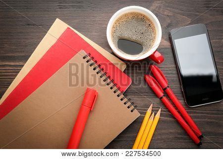 Office stationery, cup of coffee and phone on table