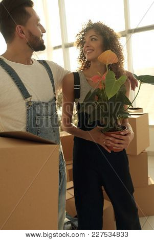 Close-up of a beautiful young couple is carrying things into a new home