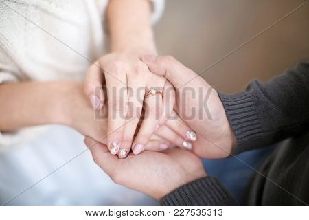Young man holding hands of his beloved wife, closeup