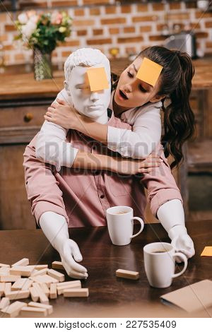 Portrait Of Woman With Sticky Note On Forehead Hugging Layman Doll At Home, Perfect Relationship Dre