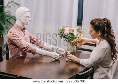 Woman Pouring Wine Into Glass While Sitting At Table With Layman Doll, Unrequited Love Concept