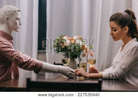 Side View Of Woman With Glass Of Wine Sitting At Table With Layman Doll, Unrequited Love Concept