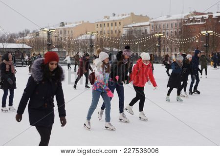 ST. PETERSBURG, RUSSIA - FEBRUARY 4, 2018: People on the public skating rink on New Holland island. There is dozens of public skating rink in the city, including few free of charge