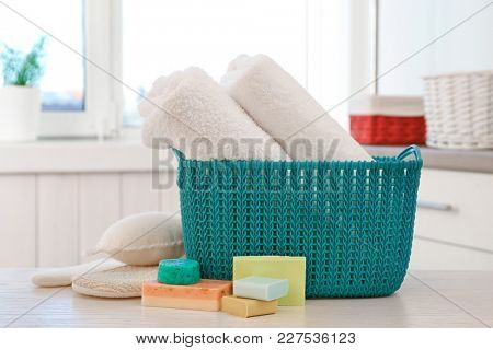 Basket with soft towels and different soap bars on table indoors