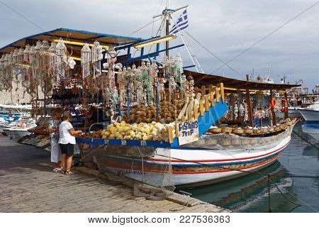 RHODES, GREECE - OCTOBER 7, 2017: People at the sea souvenir shop on the boat. Rhodes is popular tourist destination due to its medieval city