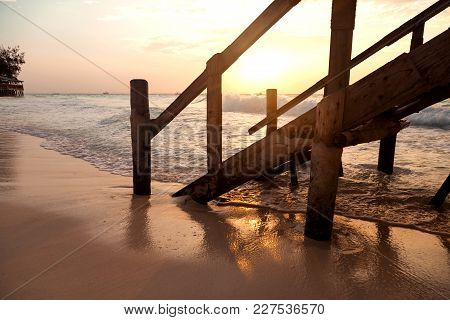 A Pier On A Sandy Beach In The Morning Light.