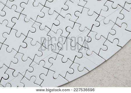 A White Jigsaw Puzzle In The Complete Form Lies On A Treated Stone Surface. Textured Image With Copy