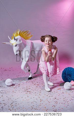 Child Fashion Concept. Romantic Girl Caucasian In Pink Dress Eats A Little Lollipop. Geometric Backg