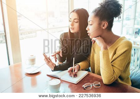 Girls Sitting Tigether Very Close To Each Other. One Of Them Is Writing Something Down In Her Notebo