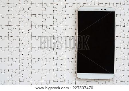 A Modern Big Smartphone With A Touch Screen Lies On A White Jigsaw Puzzle In An Assembled State