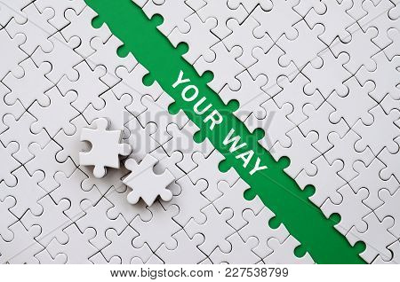 Your Way. The Green Path Is Laid On The Platform Of A White Folded Jigsaw Puzzle. The Missing Elemen