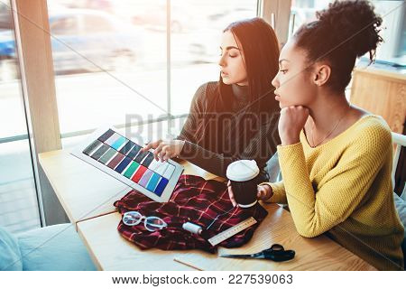Two Young Women Standing Together And Working For The Same Fashion Project. They Are Trying To Cut A